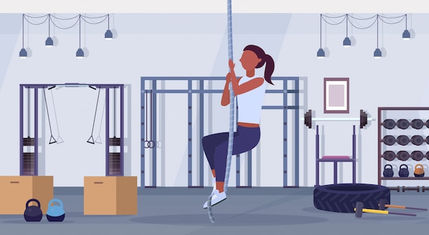 Sporty woman doing rope climbing exercise african american girl training cardio crossfit workout concept modern gym health studio club interior horizontal flat full length