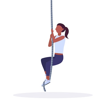 Sporty woman doing rope climbing exercise   girl training in gym cardio crossfit workout healthy lifestyle concept  white background full length