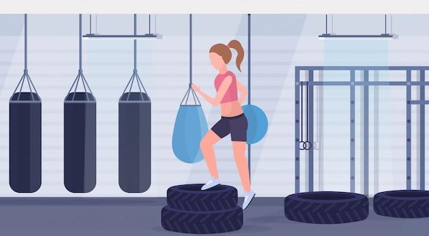 스포티 한 여자 하 고 타이어 플랫폼 소녀 훈련 다리 운동 샌드 백 현대 헬스 클럽 인테리어 가로 평면 건강 한 라이프 스타일 crossfit 개념 체육관