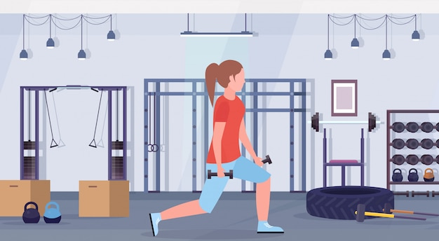 Sporty woman doing squats with dumbbells girl training in gym buttocks workout healthy lifestyle concept modern health club studio interior horizontal