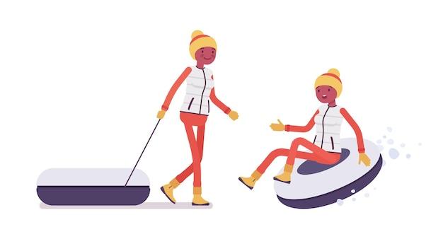 スノーチュービングを楽しむスポーティな女性