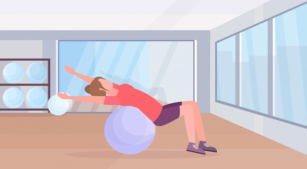 Sporty woman lying fitness ball girl doing exercises training in gym aerobic pilates workout healthy lifestyle concept flat modern health club studio interior horizontal