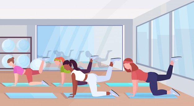 Sporty women doing fitness exercises on yoga mat mix race girls training in gym workout healthy lifestyle concept flat modern health club studio interior horizontal