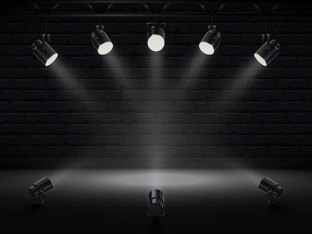 Точечные светильники с ярким белым светом светят сцене. коллекции проекторов с эффектом подсветки. комплект проектора для студии с кирпичной стеной.