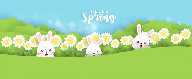 Spring banner with field of daisy and cute rabbits in paper cut and craft style.