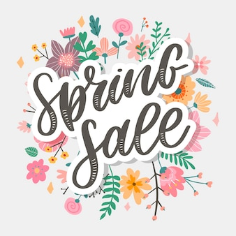 Spring sale word hanging on leaves with strings.   flowers