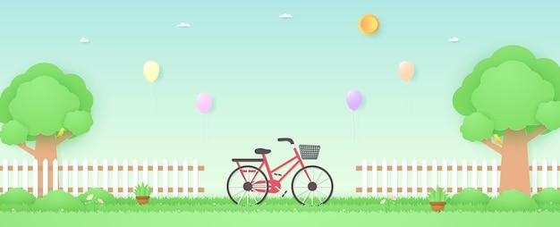 잔디에 화분과 꽃 위로 풍선이 날아가는 정원의 봄철 자전거