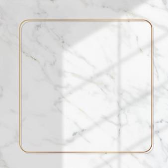 Cornice quadrata in oro con ombra della finestra su sfondo di marmo bianco
