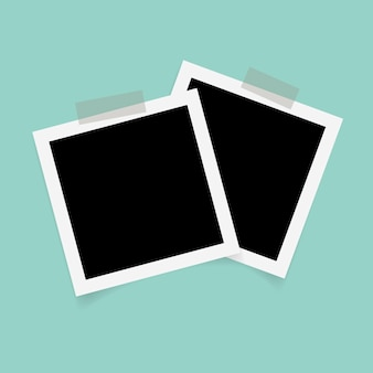 Square photo frames with sticky tape on green background.