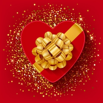 St valentines heart shaped gift box with gold ribbon and bow.