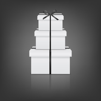 Stack of three realistic white gift boxes with black ribbon and bow
