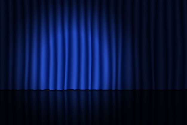 Stage with blue curtain and spotlight.