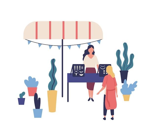 수제 장신구 또는 보석류가있는 매점 또는 카운터, 여성 판매자 및 고객