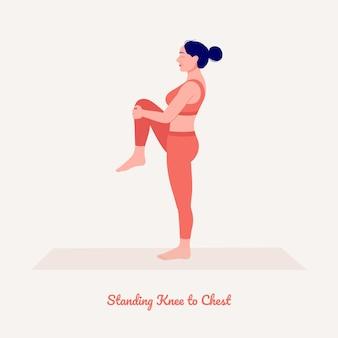 立っている膝から胸のポーズヨガの練習をしている若い女性