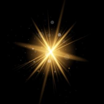 キラキラとスターバースト。黄色の輝く光のセットが黒い背景に爆発する魔法の粉塵粒子。ゴールドラメブライトスター。透明な太陽、明るいフラッシュ
