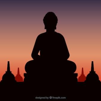 夕日と仏のシルエットの像