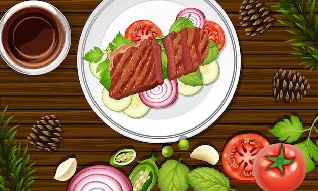 Стейк еда крупным планом на фоне стола с некоторыми овощными реквизитами