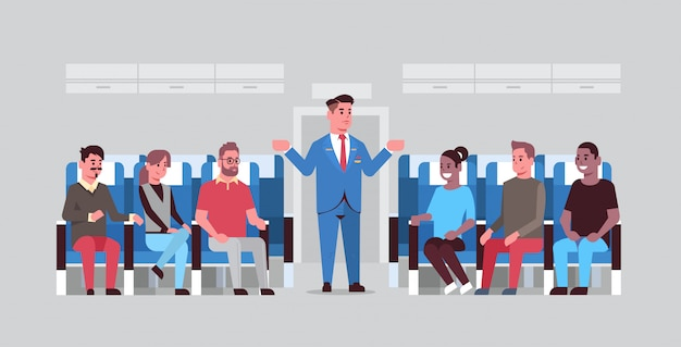 Steward explaining instructions for mix race passengers male flight attendant in uniform gesturing hands showing emergency exits safety demonstration concept airplane board interior horizontal