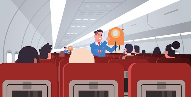 Steward explaining for passengers how to use jacket life vest in emergency situation male flight attendants in uniform safety demonstration concept modern airplane board interior horizontal flat