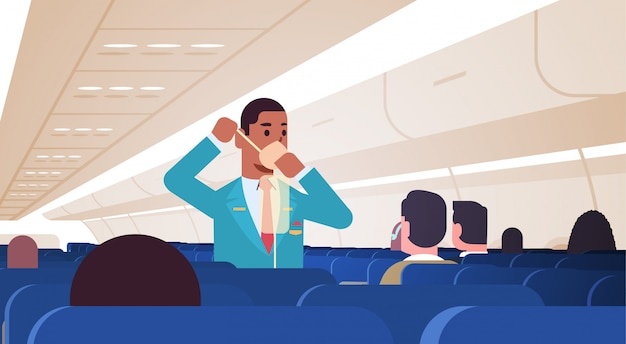 Steward explaining for passengers how to use oxygen mask in emergency situation african american male flight attendant safety demonstration concept modern airplane board interior horizontal