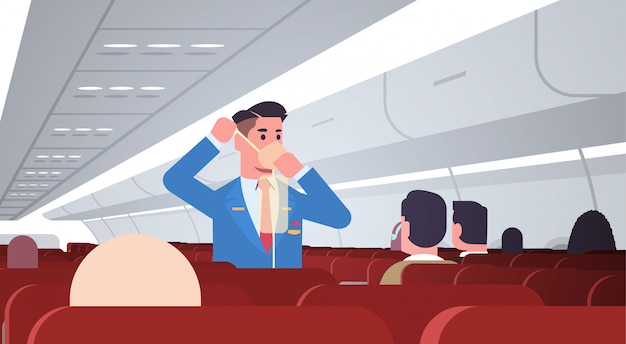 Steward explaining for passengers how to use oxygen mask in emergency situation male flight attendant safety demonstration concept modern airplane board interior