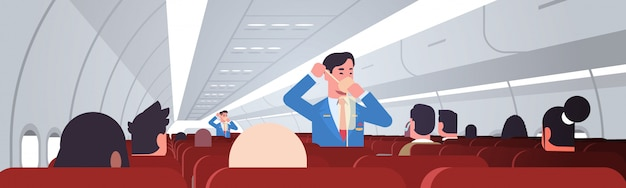 Steward explaining for passengers how to use oxygen mask in emergency situation male flight attendants safety demonstration concept modern airplane board interior