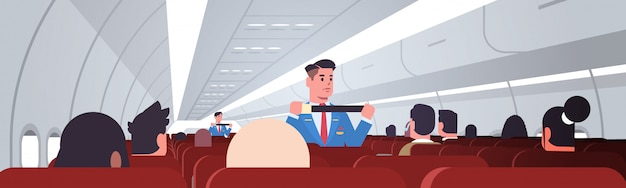 Steward explaining passengers how to use seat belt fastening in emergency situation male flight attendants in uniform safety demonstration concept airplane board interior