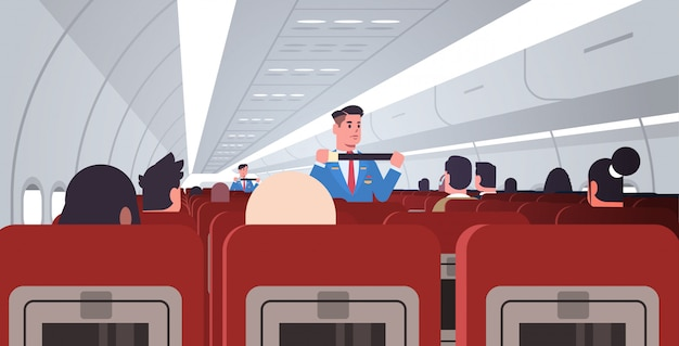 Steward explaining for passengers how to use seat belt fastening in emergency situation male flight attendants in uniform safety demonstration concept modern airplane board interior horizontal