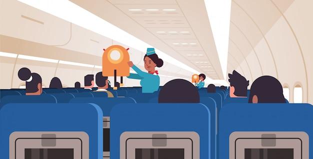 Стюардесса объясняет пассажирам, как использовать спасательный жилет в чрезвычайной ситуации афроамериканец бортпроводники безопасность демонстрация концепция современный горизонтальный самолет доска