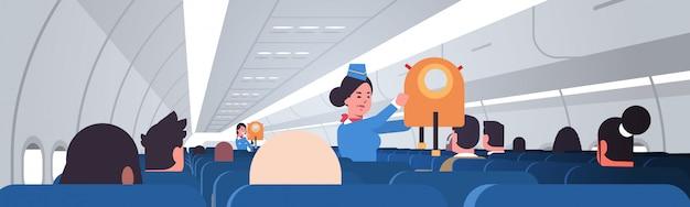 緊急事態でジャケットライフベストを使用する方法を乗客に説明するスチュワーデス女性客室乗務員の安全デモのコンセプトモダンな飛行機のボードのインテリア