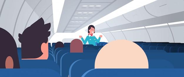 スチュワーデスが制服を着た乗客の女性客室乗務員に指示を説明し、非常口の安全デモのコンセプトを示しています飛行機のボード内部の水平