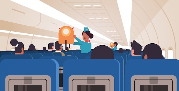 Stewardess explaining for passengers how to use jacket life vest in emergency situation african american flight attendants safety demonstration concept modern airplane board interior horizontal
