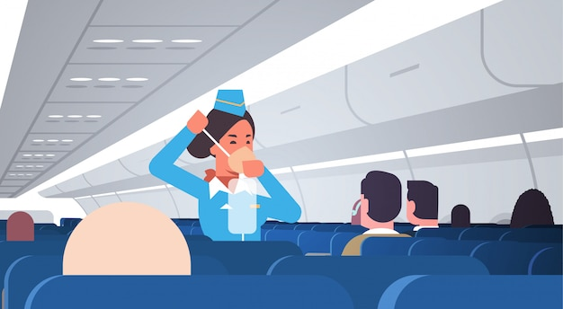 Stewardess explaining for passengers how to use oxygen mask in emergency situation flight attendant safety demonstration concept modern airplane board interior