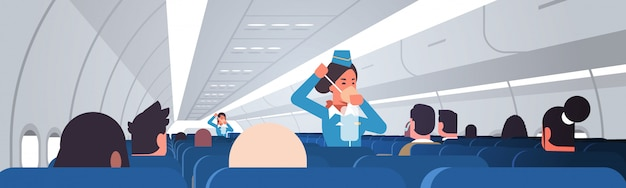 Stewardess explaining for passengers how to use oxygen mask in emergency situation flight attendants safety demonstration concept modern airplane board interior