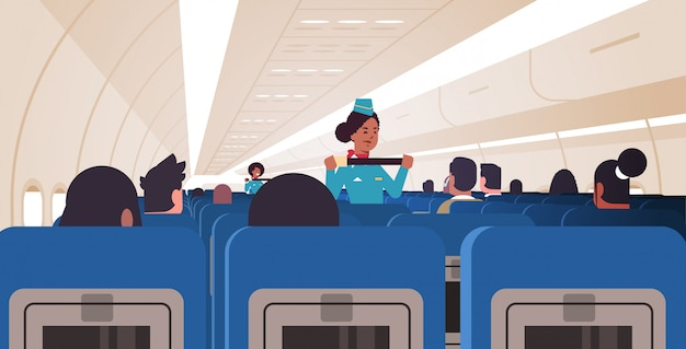 Stewardess explaining passengers how to use seat belt fastening in emergency situation african american flight attendants in uniform safety demonstration concept airplane board interior horizontal