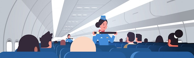 Stewardess explaining passengers how to use seat belt fastening in emergency situation flight attendants in uniform safety demonstration concept airplane board interior
