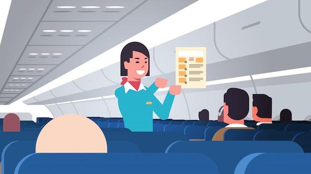 Stewardess explaining for passengers instructions card female flight attendant safety demonstration concept modern airplane board interior portrait