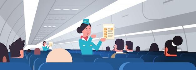 Stewardess explaining for passengers instructions card female flight attendants safety demonstration concept modern airplane board interior portrait