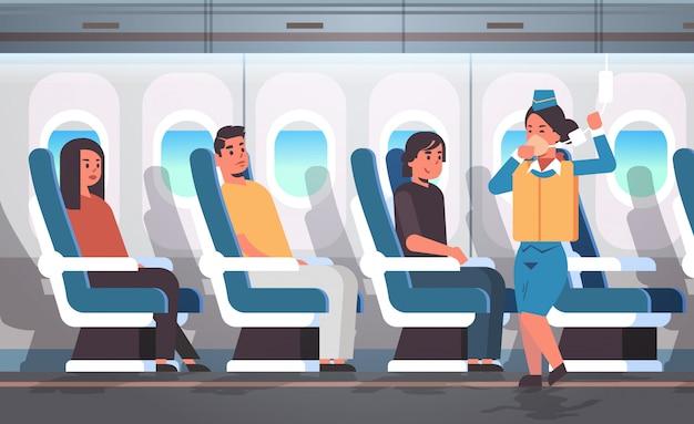 緊急時の現代の飛行機のボードインテリアで酸素マスクを使用する方法を示す乗客の客室乗務員のためのライフベスト付き安全指示を説明するスチュワーデス