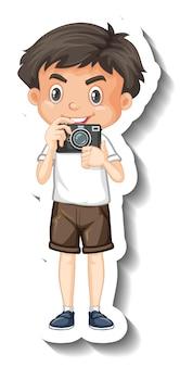 Un modello di adesivo con un ragazzo carino che tiene in mano il personaggio dei cartoni animati della fotocamera Vettore gratuito