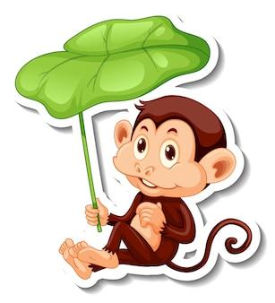 Modello di adesivo con una scimmia che tiene una foglia su sfondo bianco