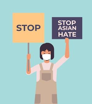 Остановить азиатскую ненависть. девушка в маске держит плакаты против расизма. поддержать людей во время пандемии коронавируса covid-19