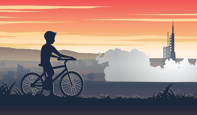 Рассказ о силуэте мальчика, который едет на велосипеде и останавливается, чтобы посмотреть, запускает ли ракету.