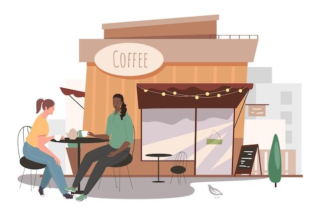 거리 카페 건물 웹 개념입니다. 카페테리아 테이블에 앉아 커피를 마시는 두 여자. 아침 식사를 위해 친구 만나기