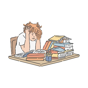 Stressed school student sitting at table with pile of books and studying.