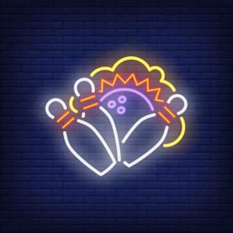 ボウルとボールを打つネオンサイン。夜の明るい広告。