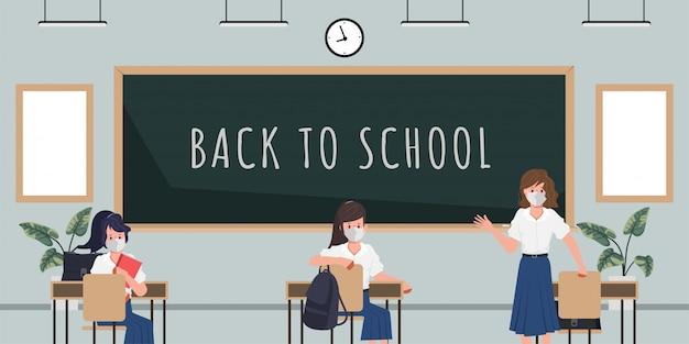 新しい通常のコンセプトで学校に戻る学生。教室の黒板背景。