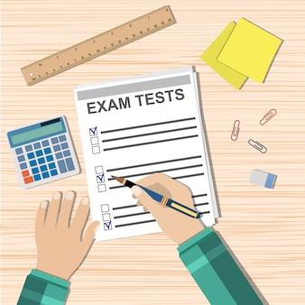 Student hand fills examination quiz paper