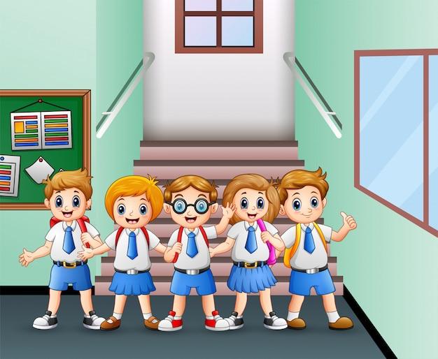 Студент в форме стоит в школьном коридоре
