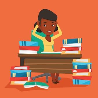 Студент сидит за столом с кучами книг.